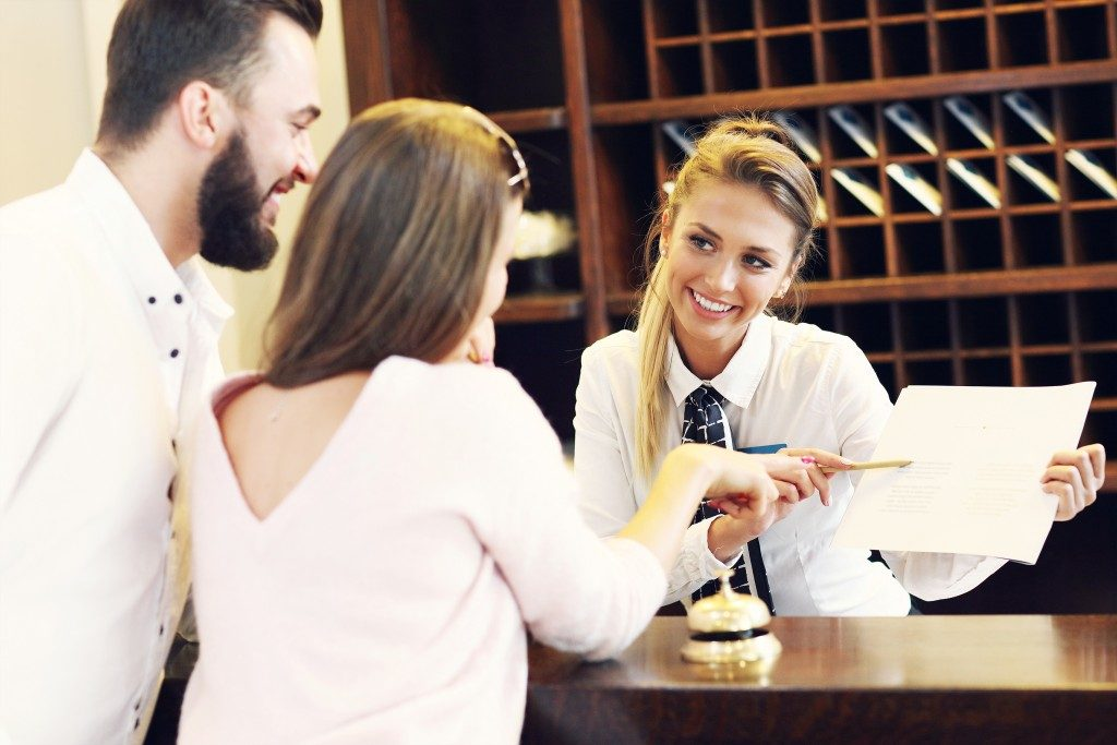 Couple asking receptionist for bar recommendation
