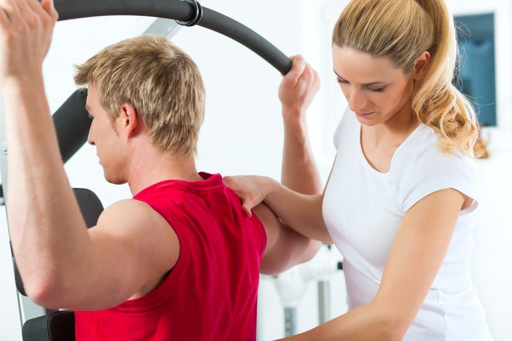 man building muscles with trainer guidance